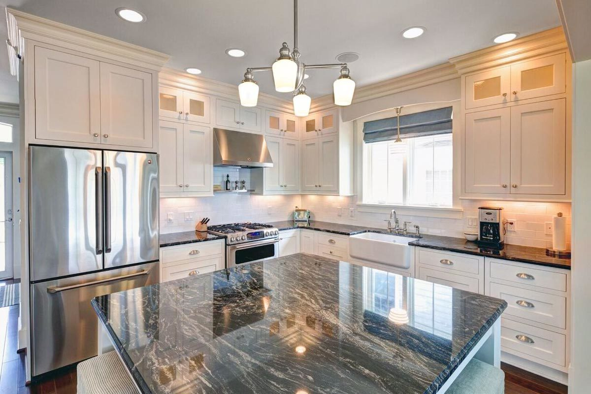 The kitchen is equipped with stainless steel appliances, farmhouse sink, white cabinets, and a granite top island.