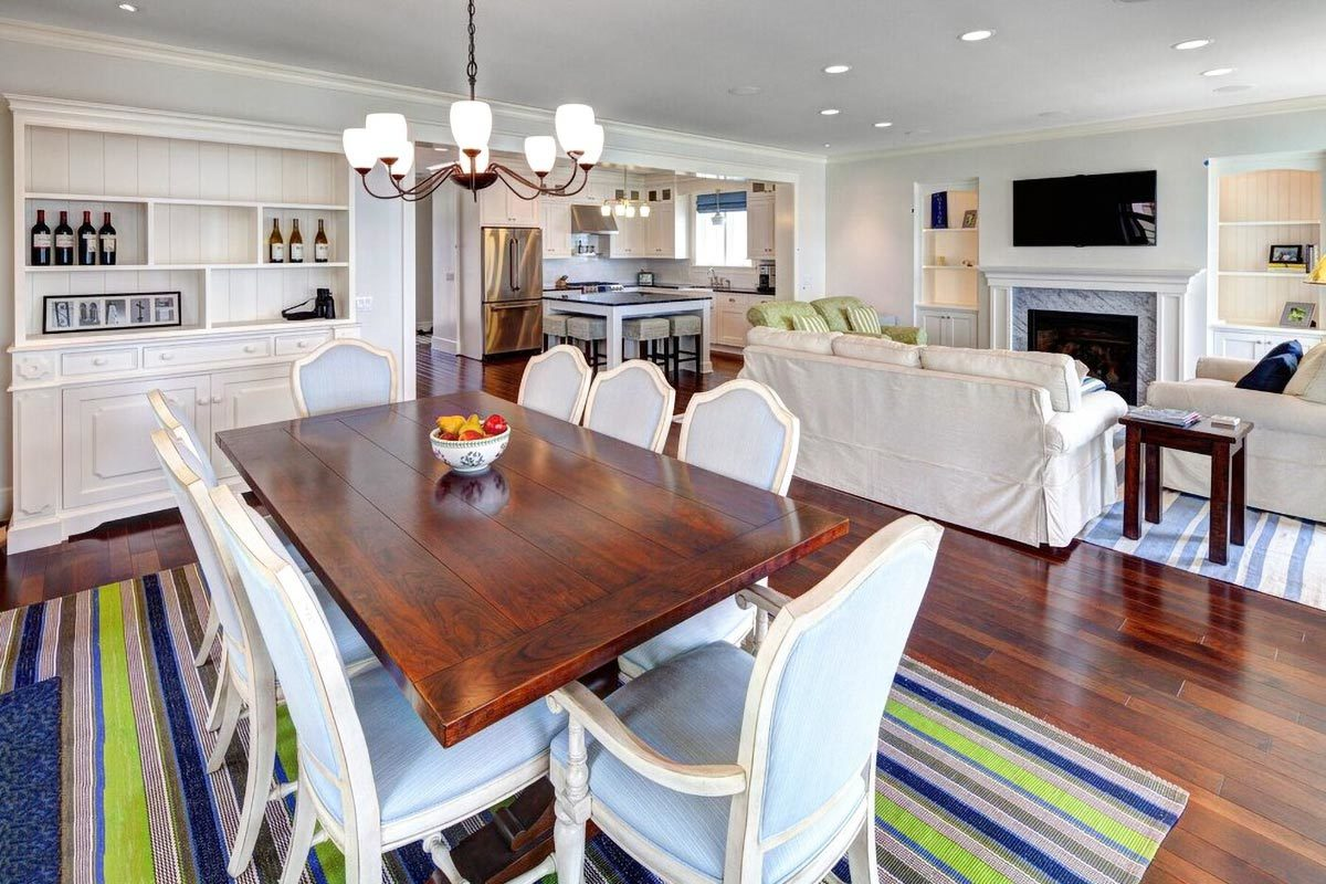 Dining area with a built-in cabinet, a glass chandelier, blue cushioned chairs, and a wood plank table sitting on a striped area rug.