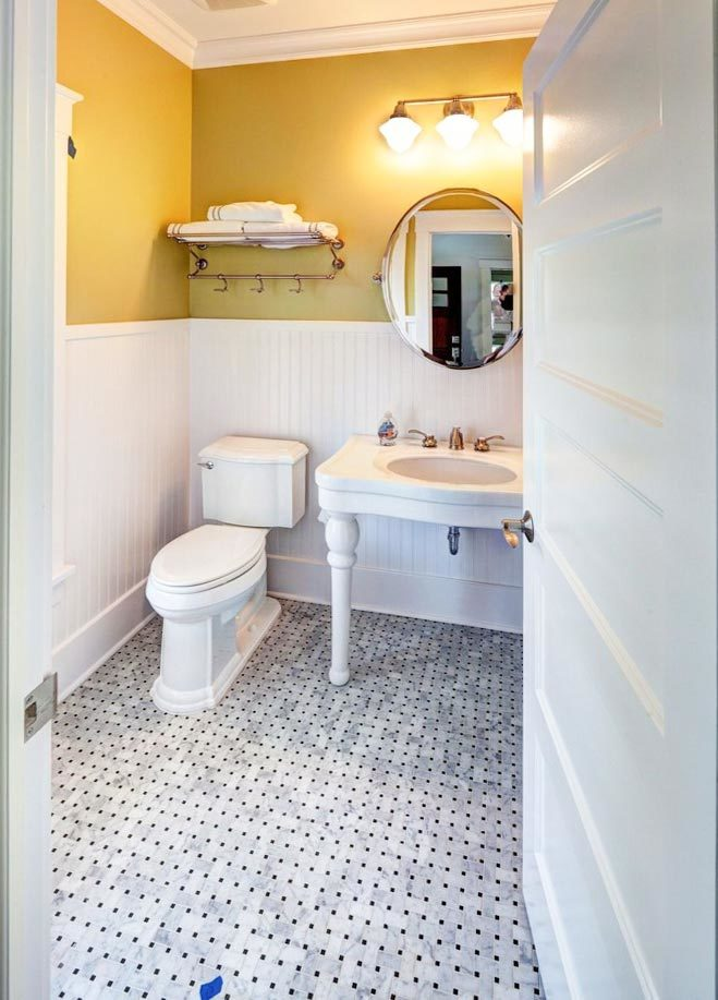 The powder room has a toilet and a washstand paired with a round mirror.