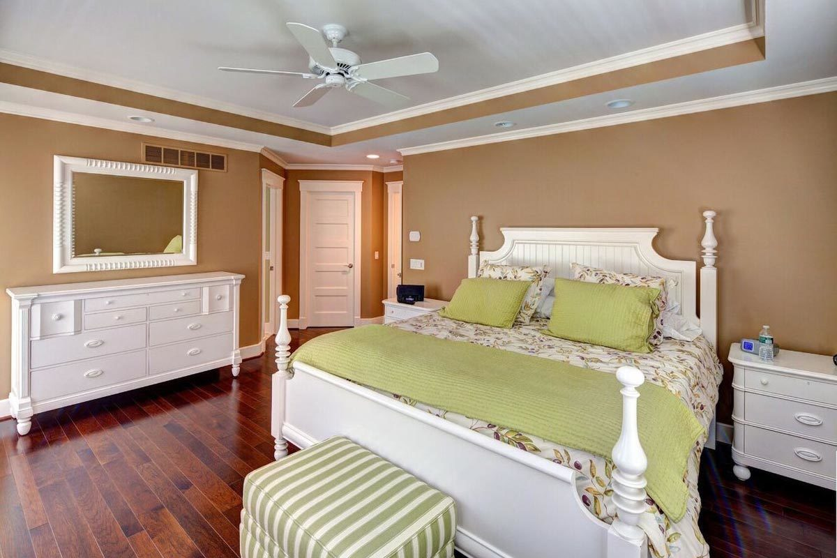 Primary bedroom with white furnishings, hardwood flooring, and a tray ceiling.