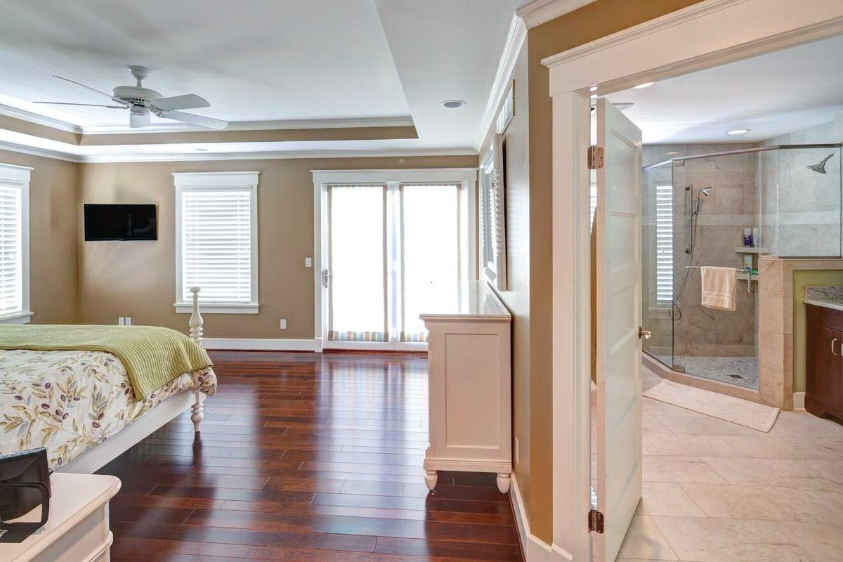 Glass doors at the back lead to a private deck while the white door on the side opens to the primary bathroom.