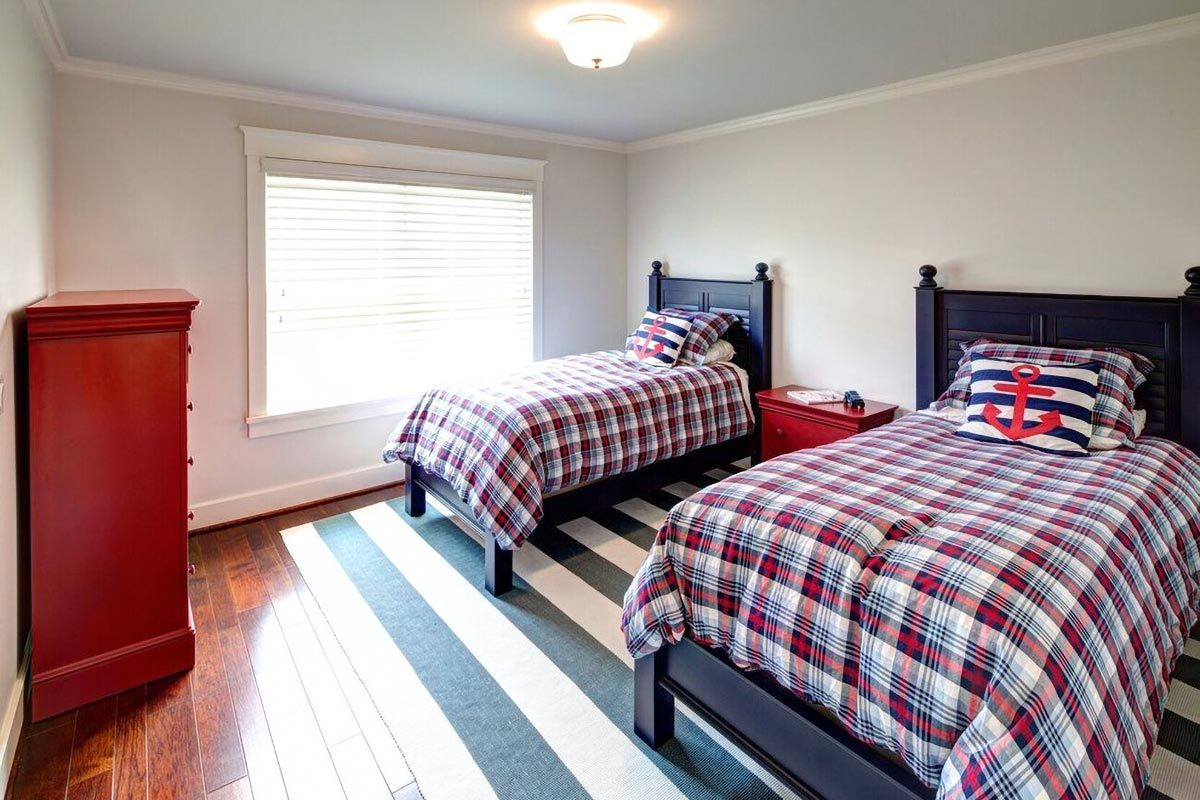 This bedroom offers two beds, a striped rug, and a center nightstand that matches the wooden dresser.