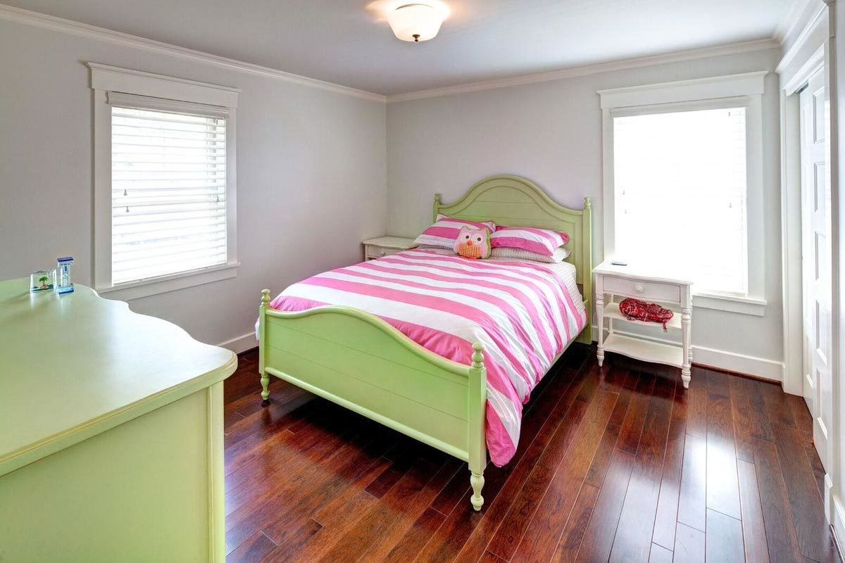 Kid's bedroom with green dresser and a matching bed flanked with white nightstands.