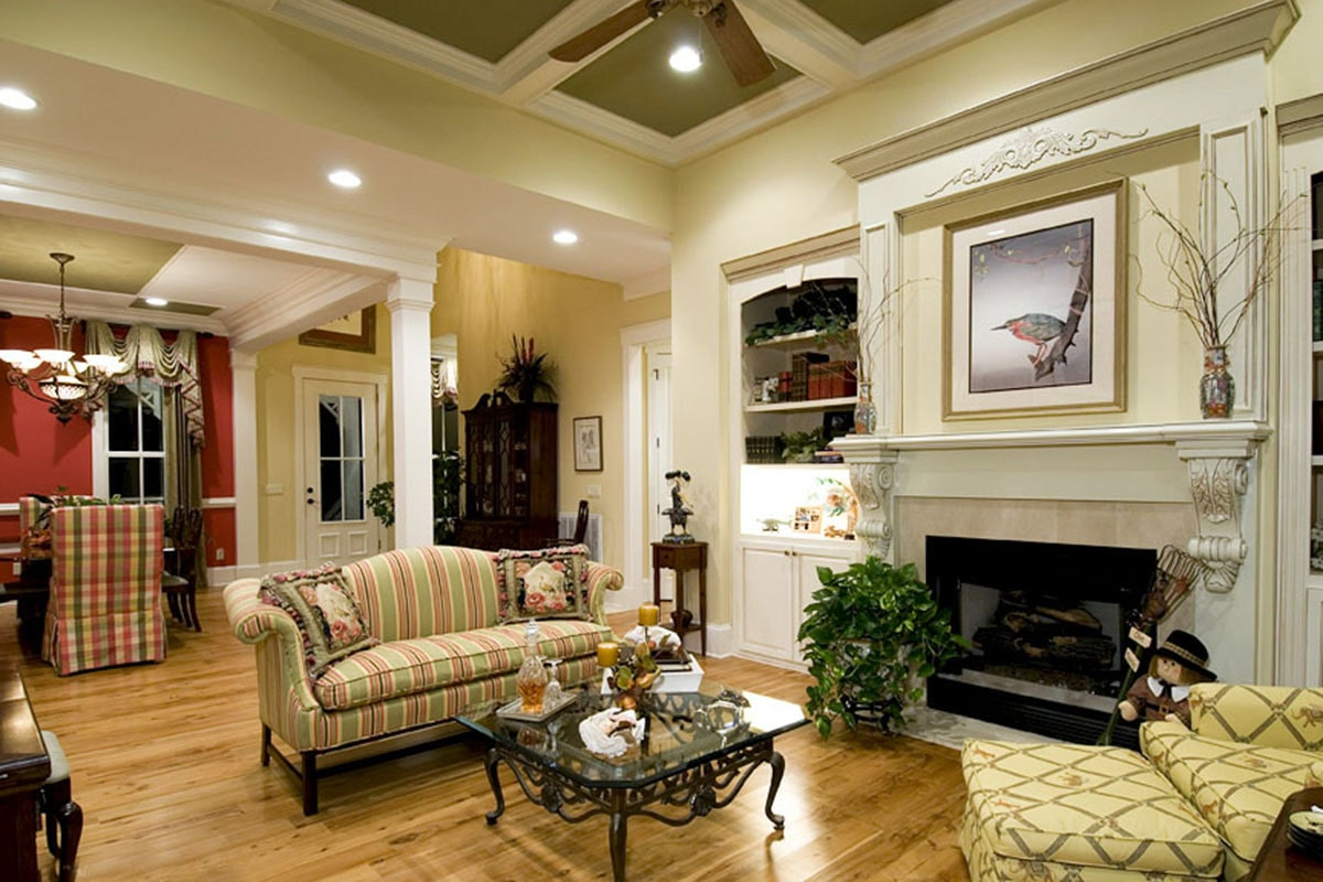 Living room with striped and patterned seats, glass top coffee table, marble fireplace, and white built-ins.