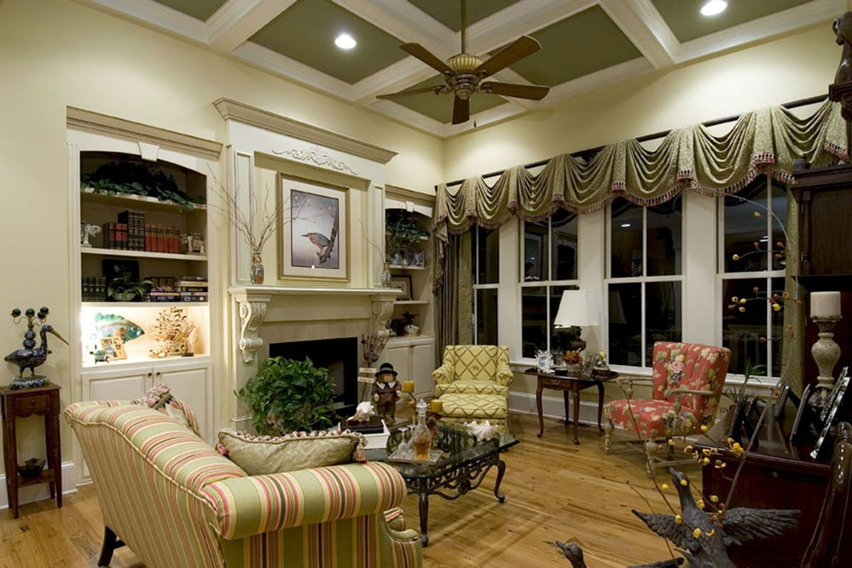 Green coffered ceiling and white framed windows dressed in classic valances complete the living room.