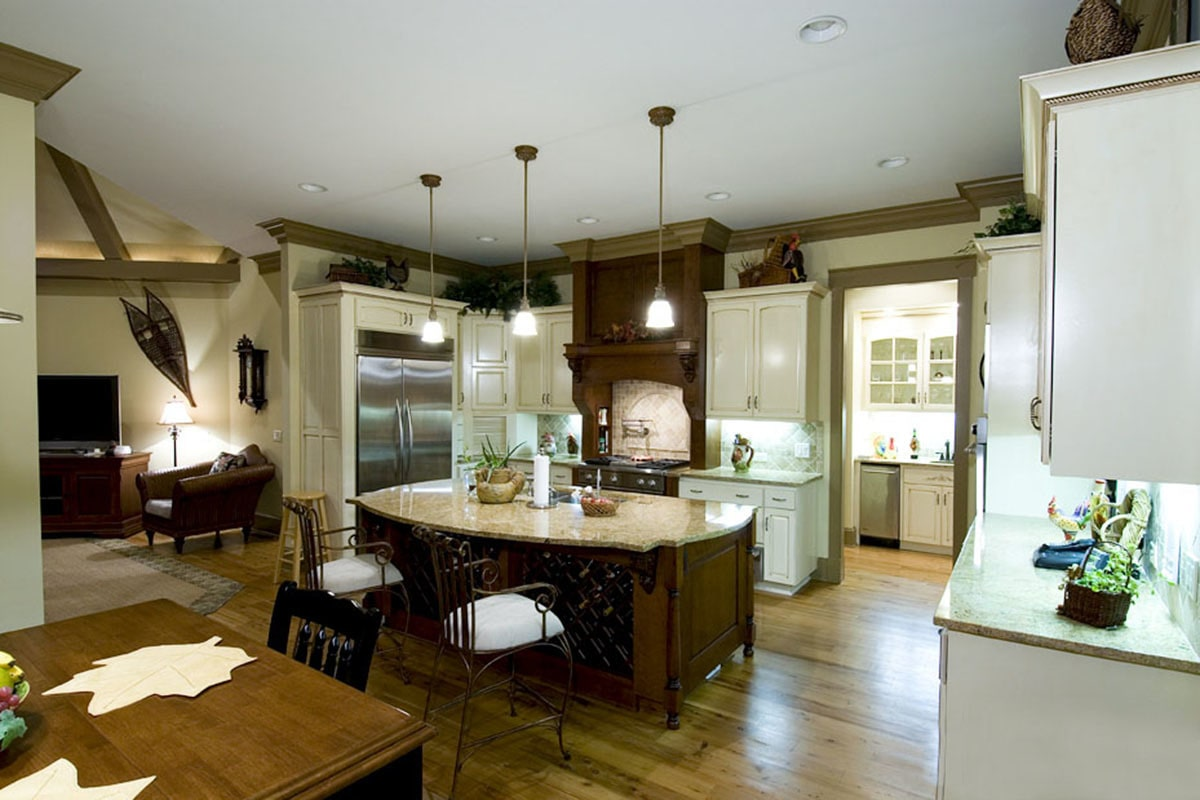 A farther view of the kitchen showing the keeping room on the side and dining area in front.
