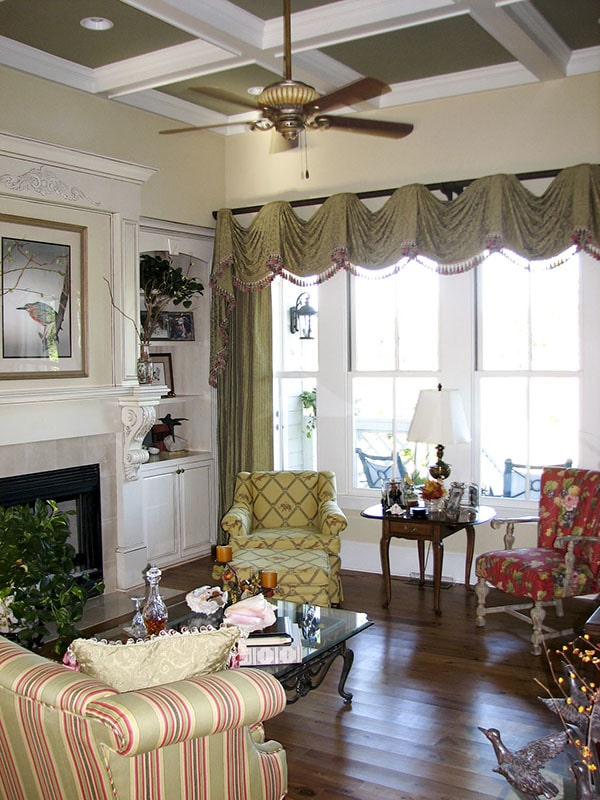 Ample natural light flows in the living room through the large white-framed windows.
