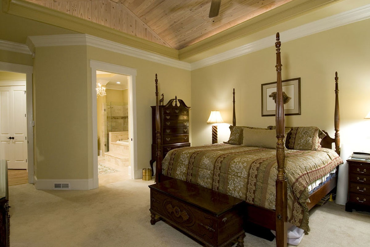 Primary bedroom with a lavish ensuite, four-poster bed, and a wood-paneled ceiling.
