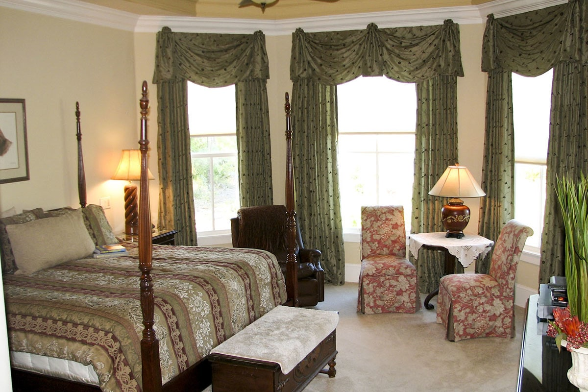 The primary bedroom includes floral chairs and a leather recliner situated by the bay window.