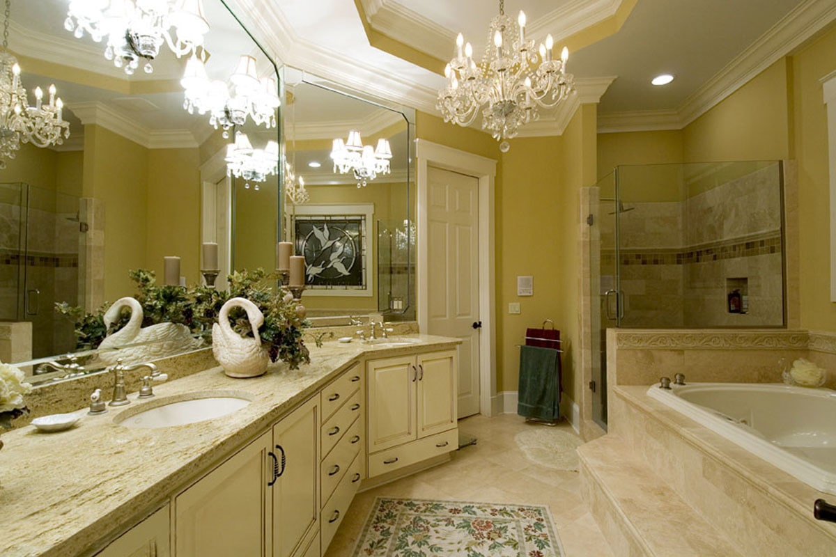 The primary bathroom has crystal chandelier and sconces, dual sink vanity, a walk-in closet, and a deep soaking tub.