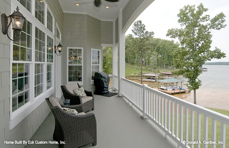 Upper balcony overlooking a breathtaking lake view. It has wicker armchairs and outdoor sconces.