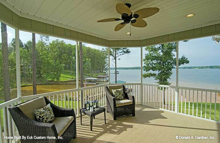 The screened porch has wicker cushioned chairs and a ceiling fan mounted on the wood plank ceiling.
