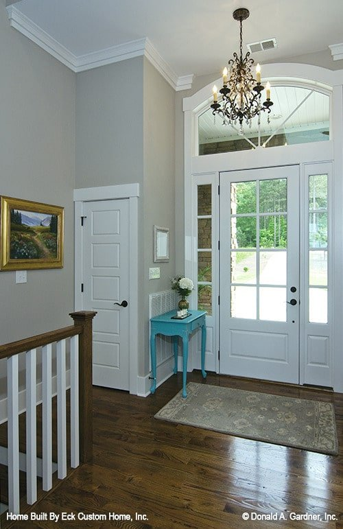 Foyer with white glazed entry door, ornate chandelier, blue console table, and a floral rug.