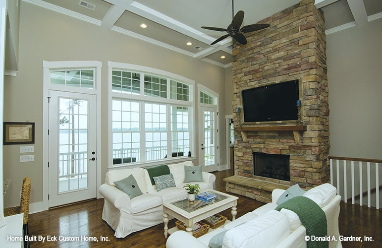 The living room offers white skirted sofas, a glass top coffee table, and a stone fireplace topped with a wall-mounted TV.