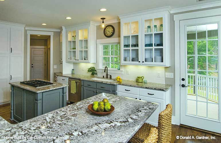 The kitchen is equipped with granite countertops, glass-front cabinets, undermount sink, and a small center island.