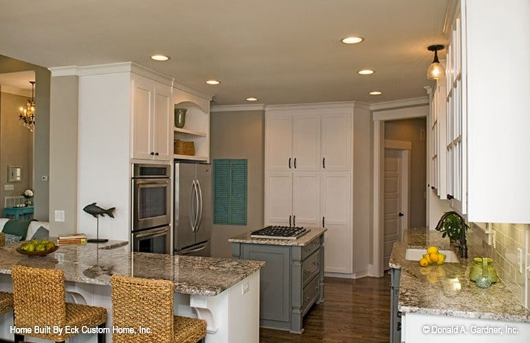 A farther view shows the double wall oven and a stainless steel fridge.