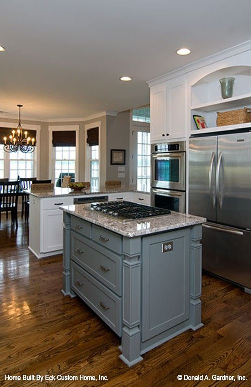 The small gray island is fitted with built-in drawers and a cooktop.