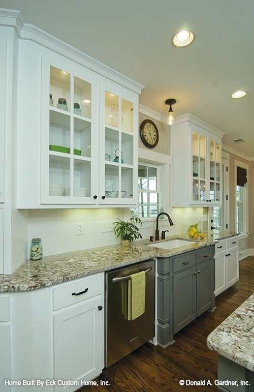 The glass-front cabinets are fixed above the granite counter and sink.