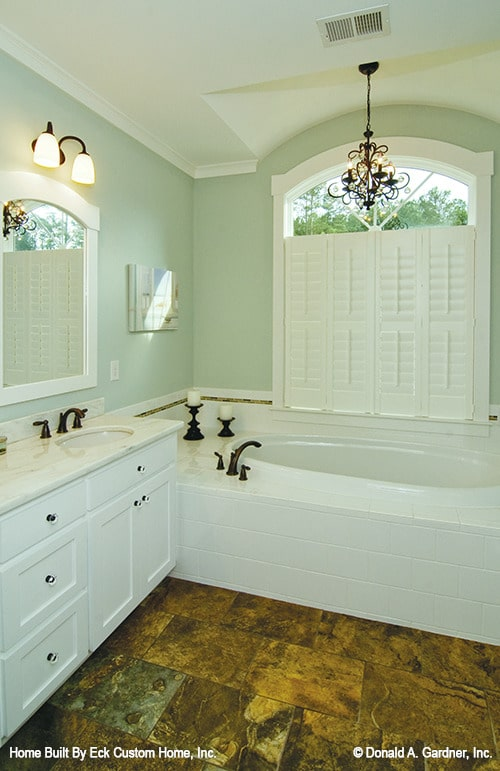 The primary bathroom has a white vanity and a deep soaking tub illuminated by an ornate chandelier.