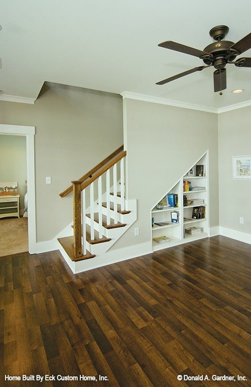 The basement has dark hardwood flooring, beige walls, and built-in shelves fitted below the staircase.