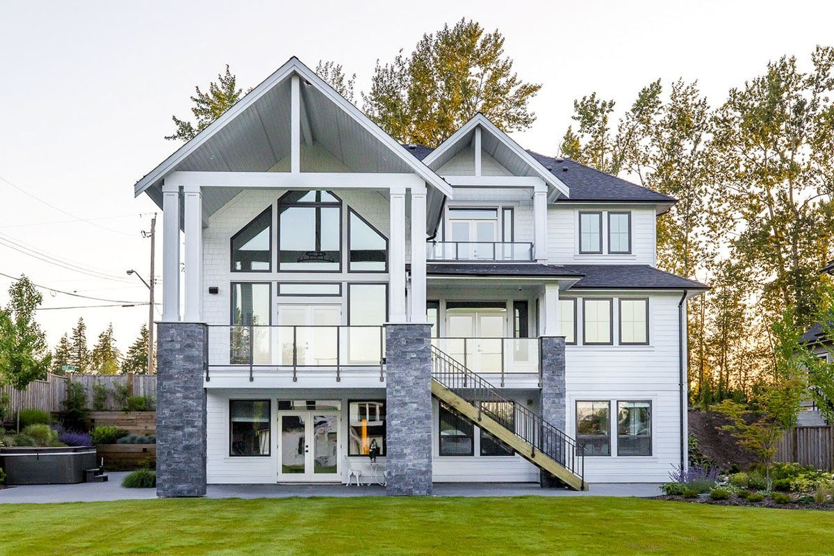 Rear exterior view with covered patio and expansive deck bordered by glass railings.