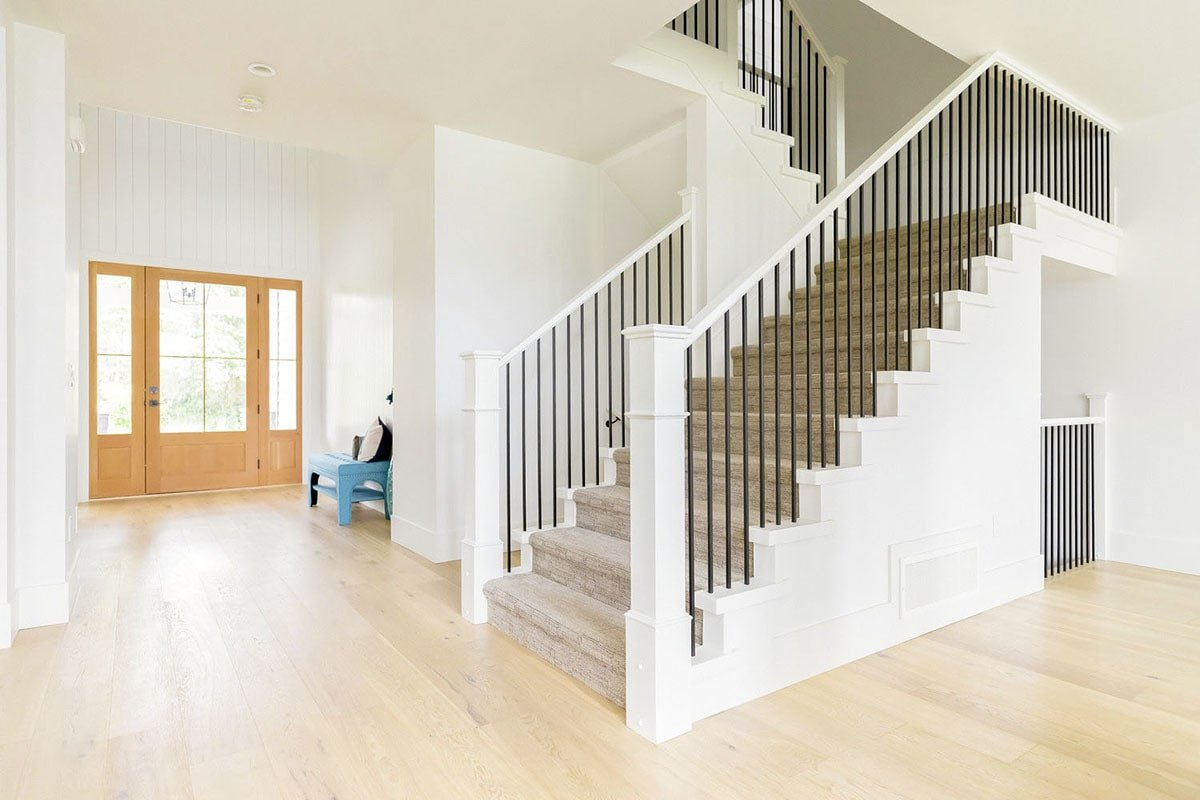 Spacious foyer with wooden glazed entry door, a blue cushioned chair, and a carpeted staircase.