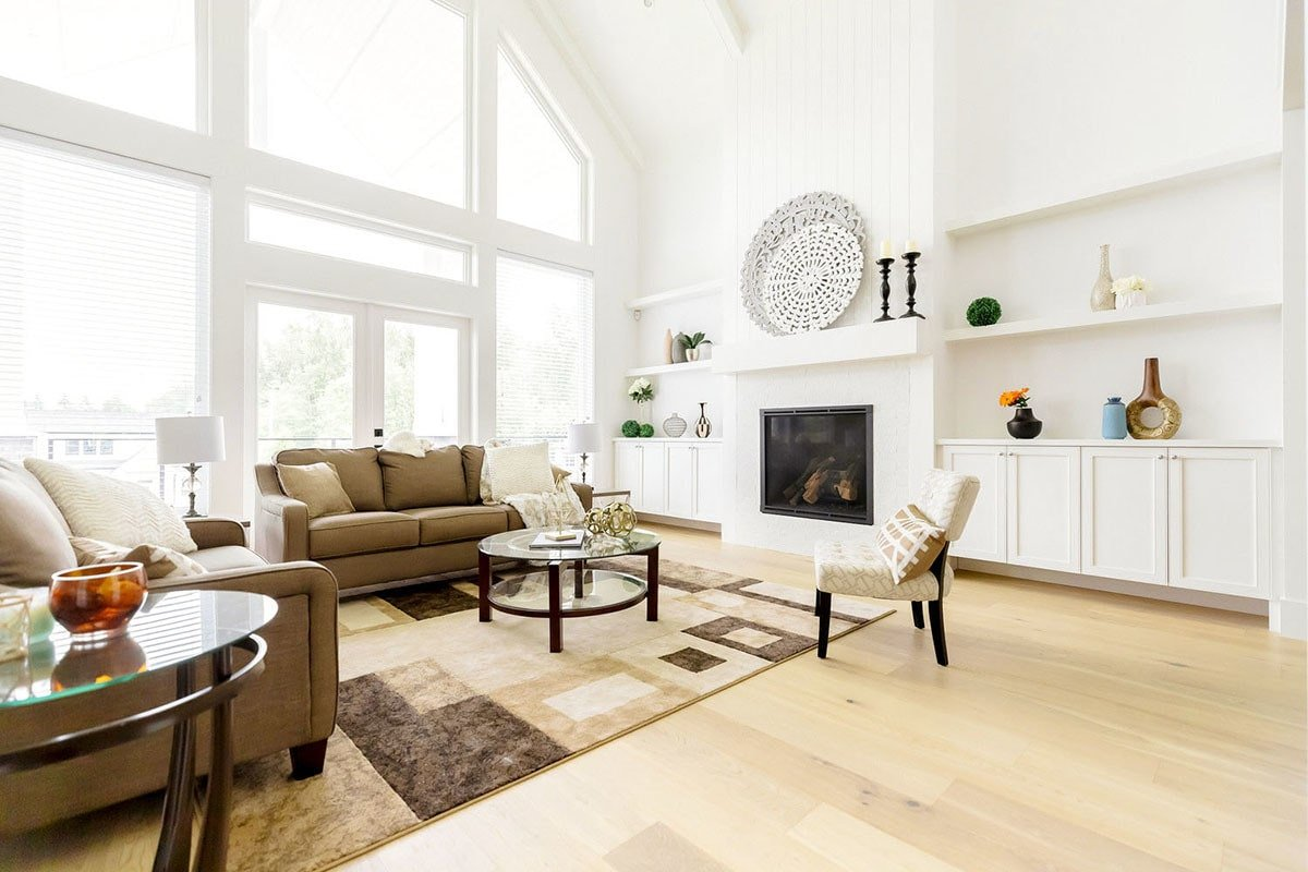 The living room has brown sofas, a round glass top coffee table, and a glass-enclosed fireplace.