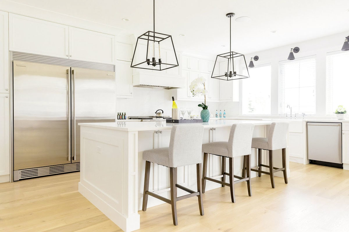 The kitchen is equipped with stainless steel appliances, quartz countertops, white cabinets, and a breakfast island.