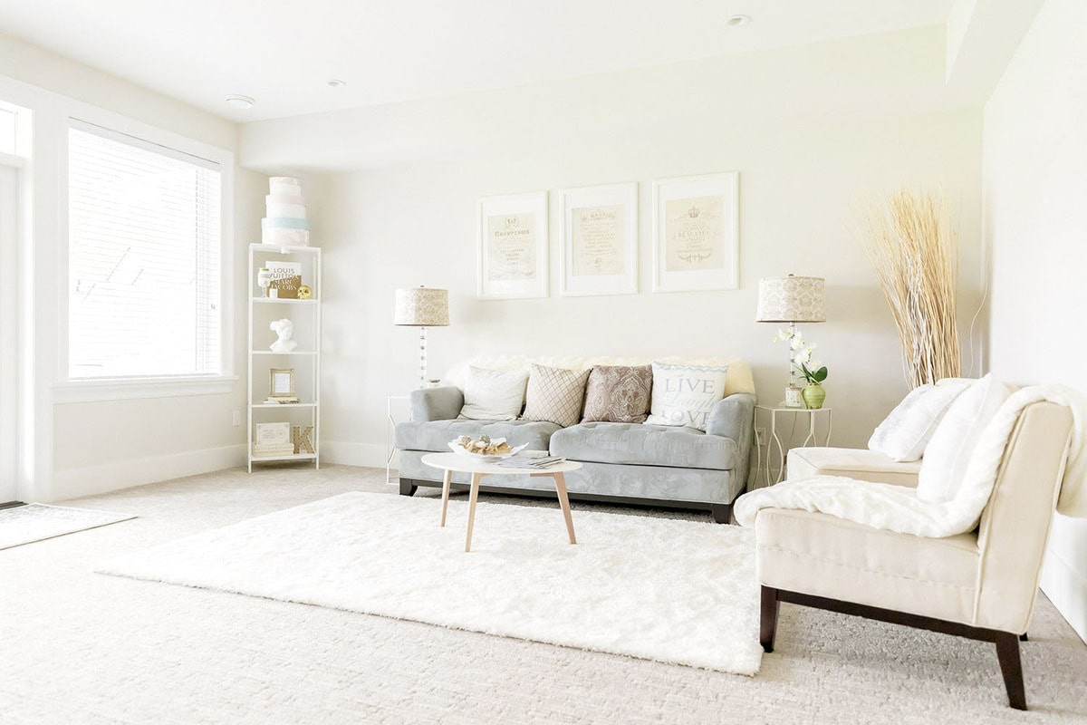 Sitting room with gray tufted sofa, beige upholstered chairs, and a white plush area rug.