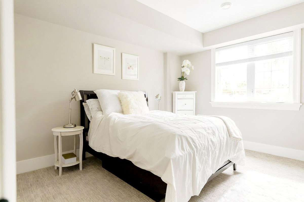 The primary bedroom has a dark wood bed, white tables, and light gray walls adorned by framed artworks.