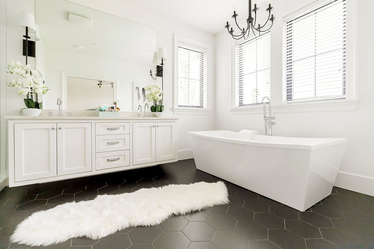 Primary bathroom with a dual sink vanity, a freestanding tub, and a faux fur rug that lays on the black hex tile flooring.