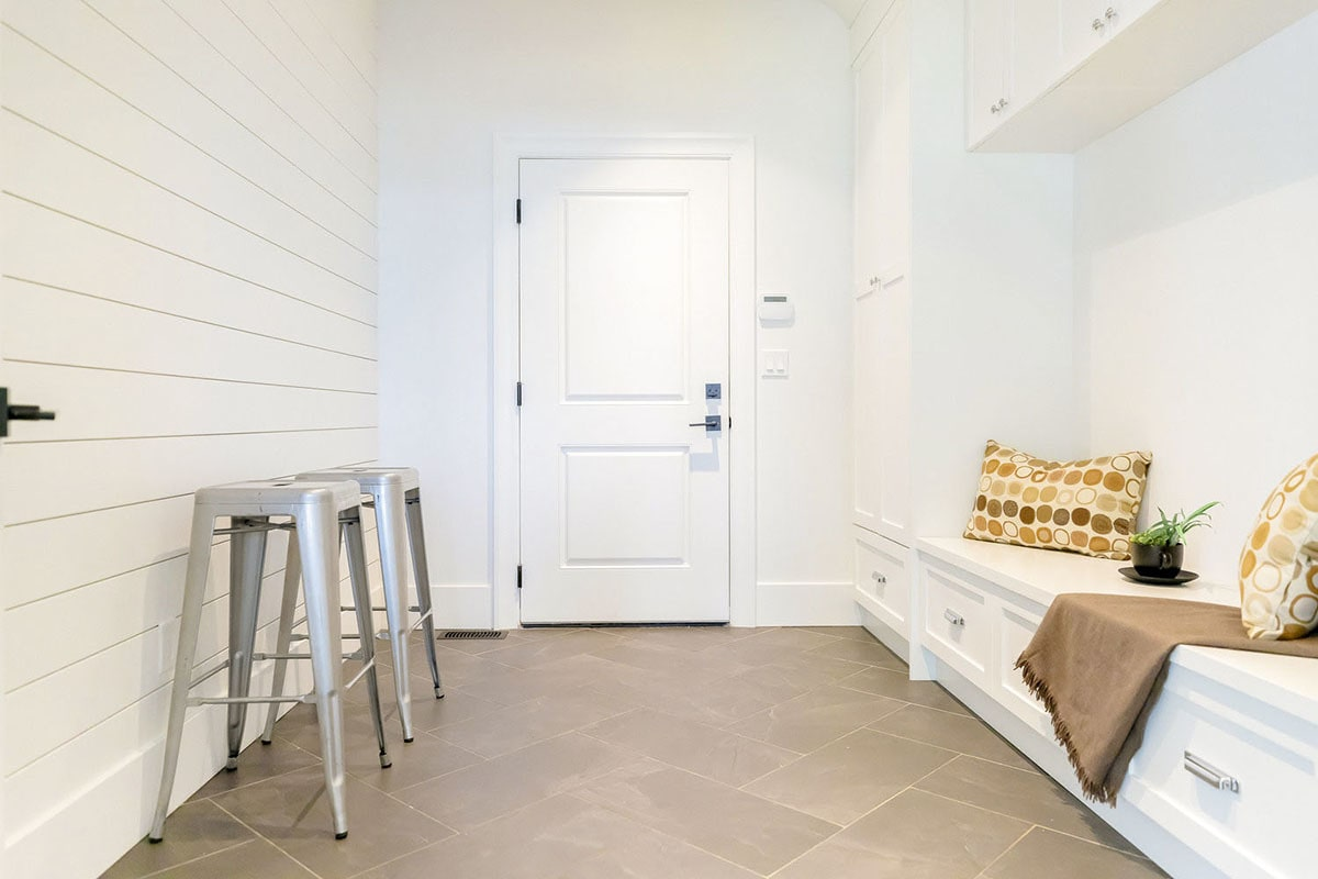 The mudroom is filled with gray stools, white built-ins, and a storage bench accentuated by patterned pillows.
