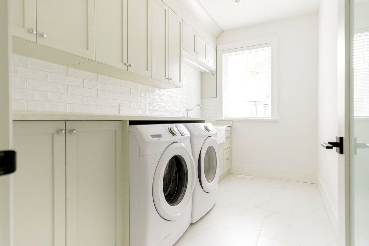 Laundry room with white cabinets, undermount sink, and front load appliances.