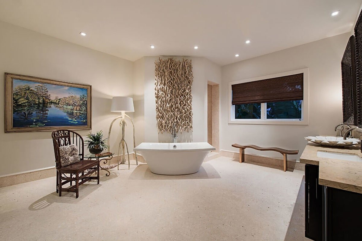 The primary bathroom has a sink vanity, walk-in shower, and a freestanding tub adorned with a driftwood wall art.