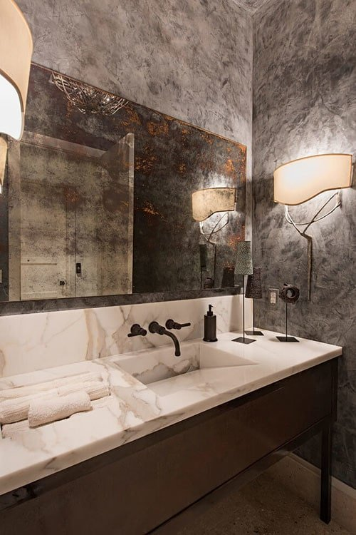 This bathroom features a marble top vanity with wrought iron fixtures and a distressed mirror that blends in with the concrete wall.