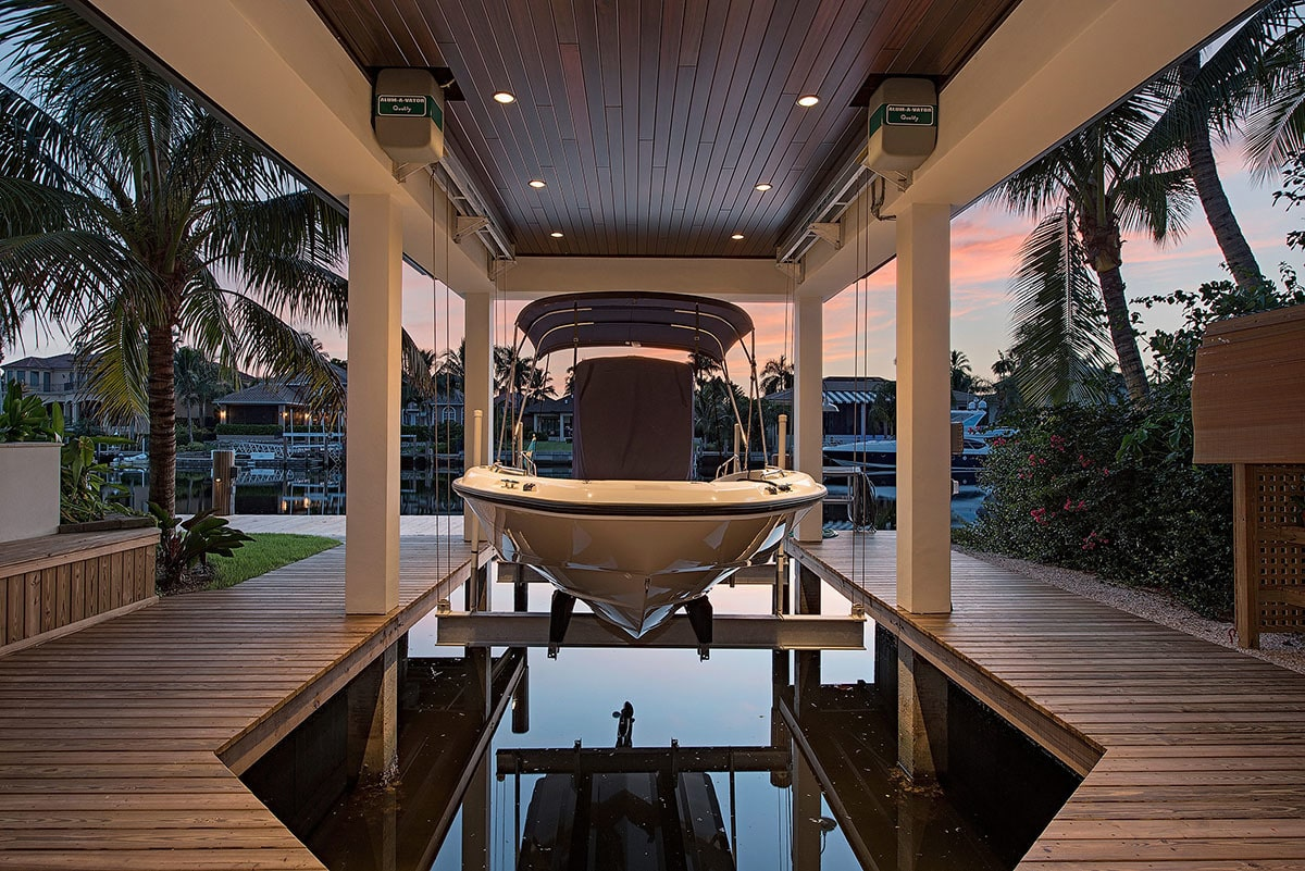 Boat house with white pillars, wood paneled ceiling, and a wooden deck.