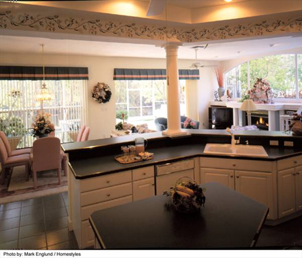 The eat-in kitchen has white cabinets, black granite countertops, center island, and a two-tier peninsula topped with a white column.