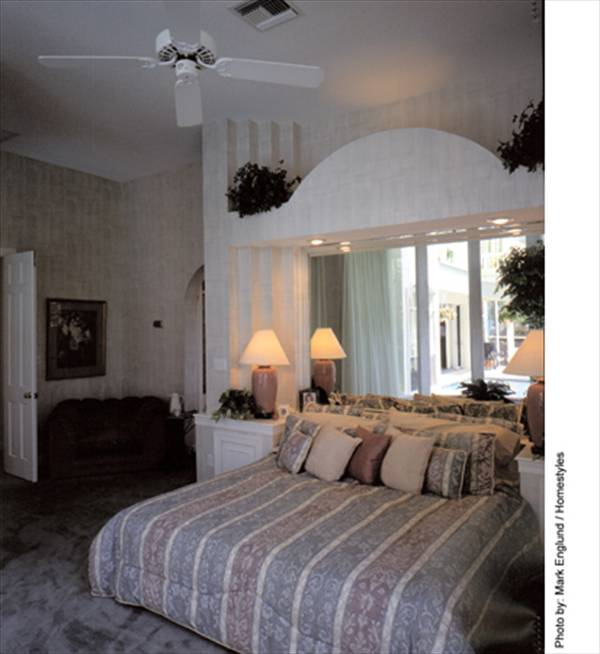 The primary bedroom offers a white ceiling fan and a cozy bed flanked by matching nightstands.