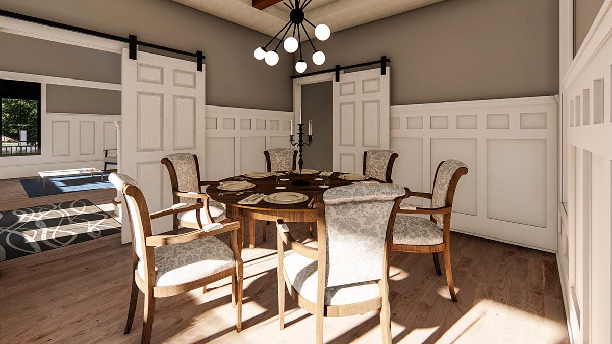 Formal dining room with sputnik chandelier, round dining set, barn doors, and gray walls adorned with white wainscoting.