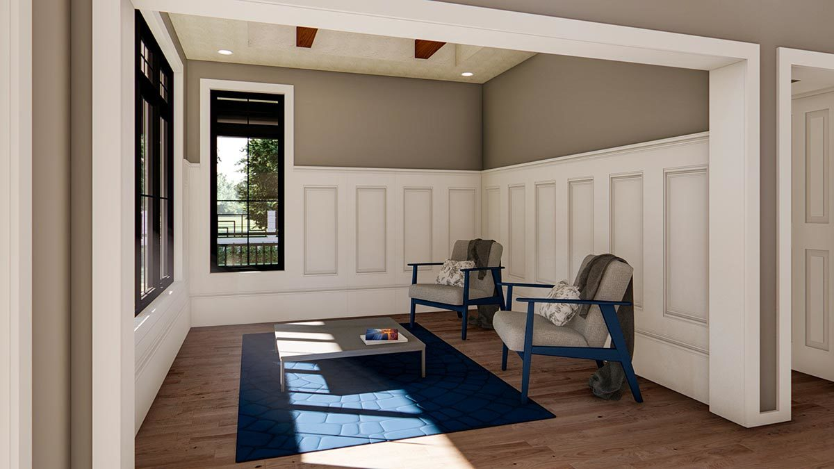 Living room with a pair of cushioned chairs and a low coffee table that sits on a blue area rug.
