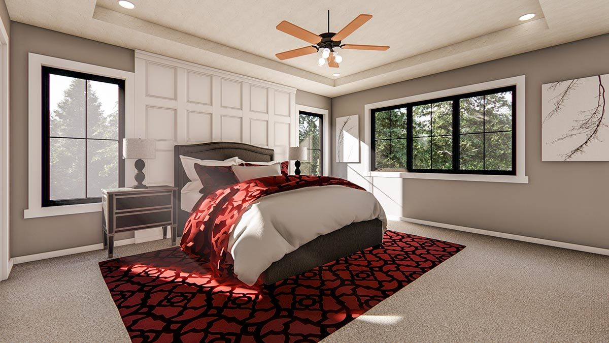 Primary bedroom with black aluminum framed windows, tray ceiling, gray upholstered bed, and a red patterned rug that stands out against the carpet flooring.