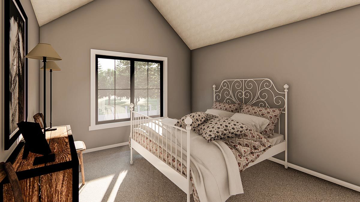 This bedroom has a cathedral ceiling, a white metal bed, and a wooden dresser placed under the framed artwork.