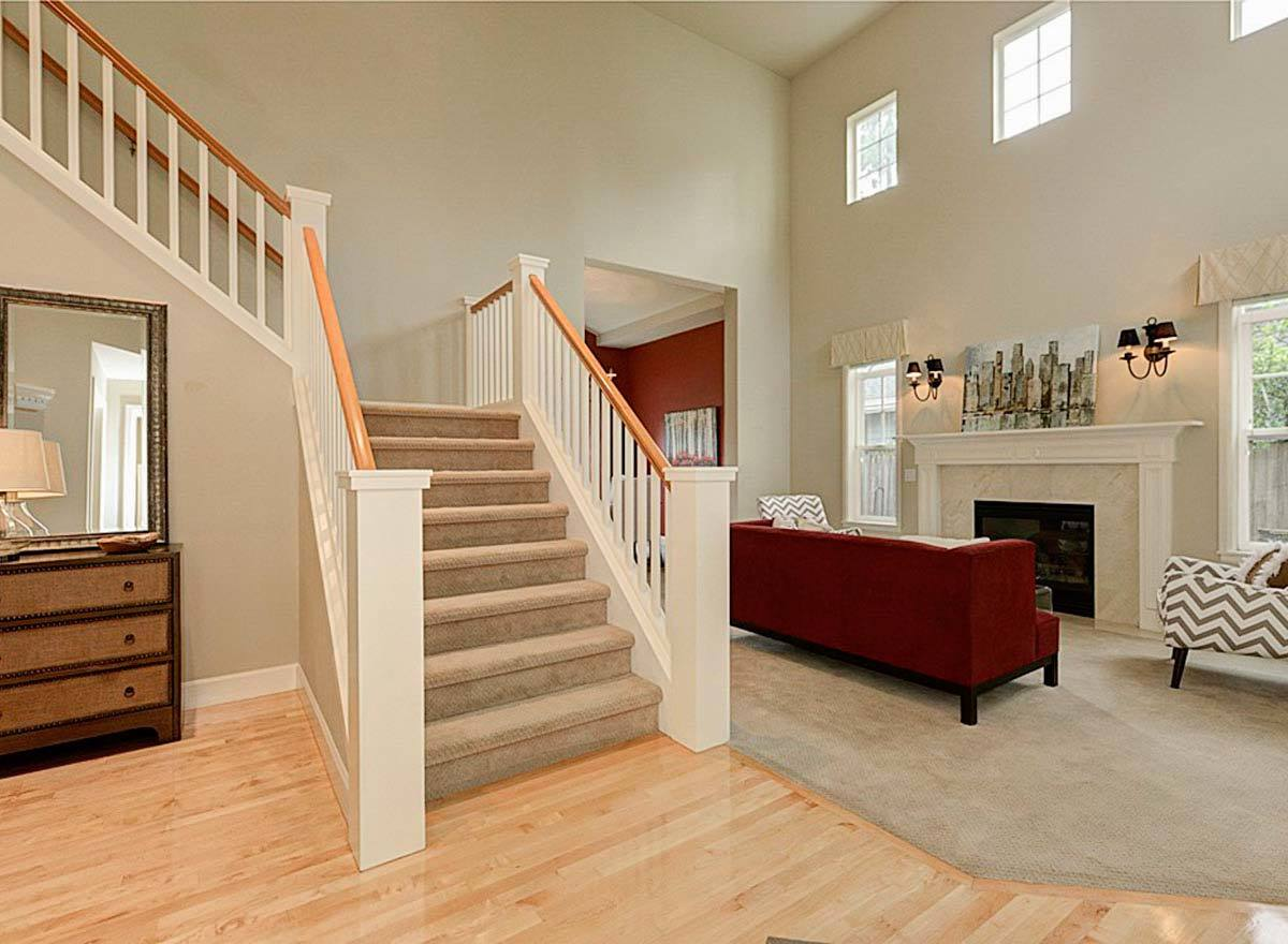 A half-turn staircase covered in beige velvet carpet is situated behind the living room.