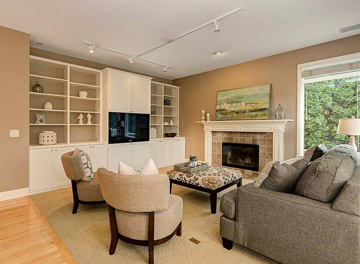 Family room with fabric seats, glass-enclosed fireplace, and a TV nestled in between the white built-ins.