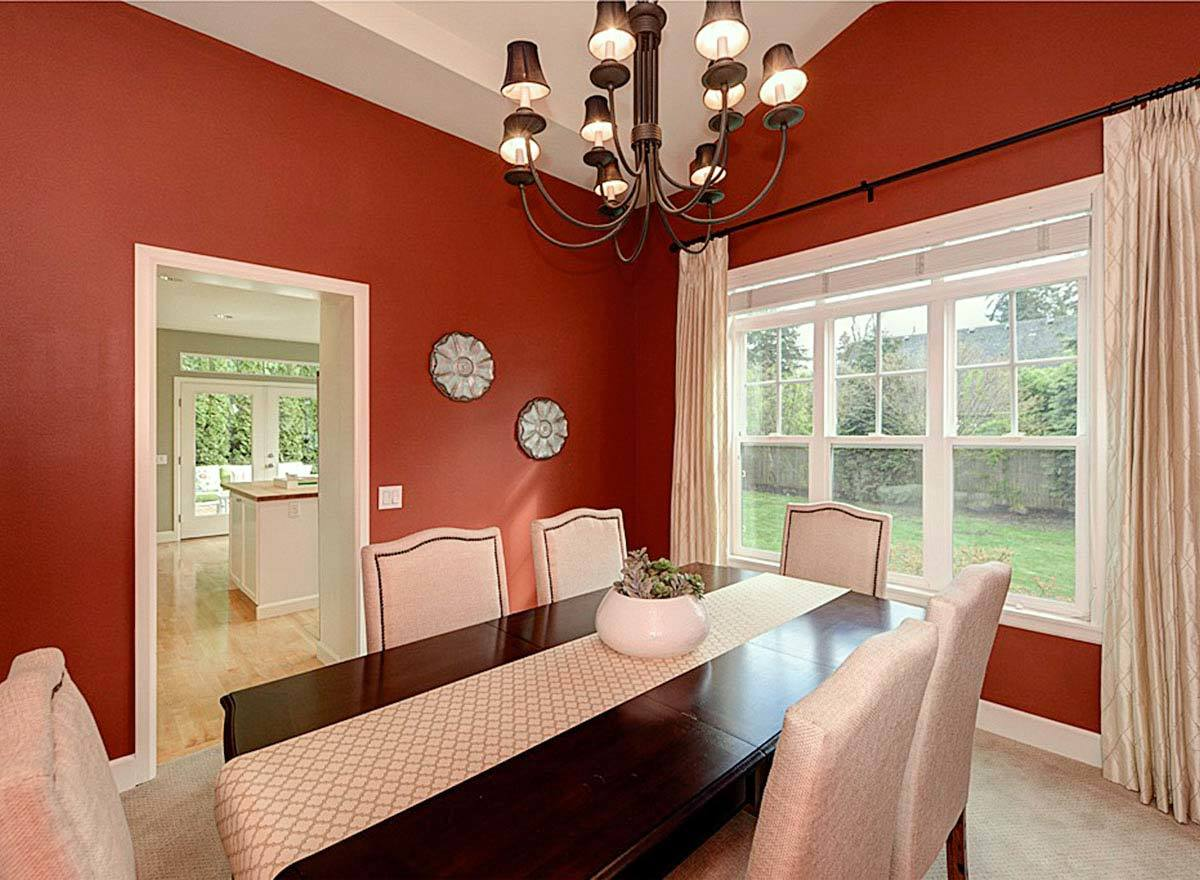 Formal dining room with red walls, beige upholstered chairs, and a dark wood dining table lined with a patterned runner.