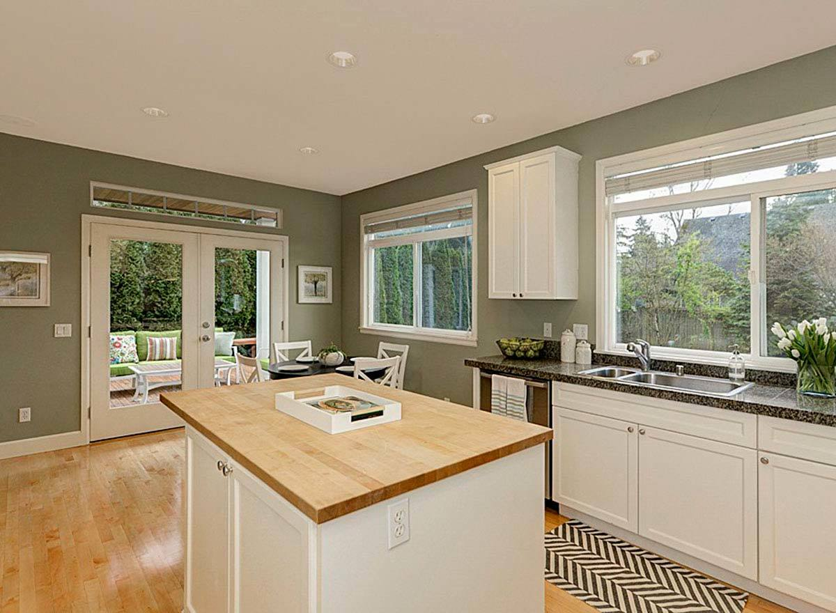 The kitchen has sage green walls, white cabinets, black granite countertops, and a wood top center island.