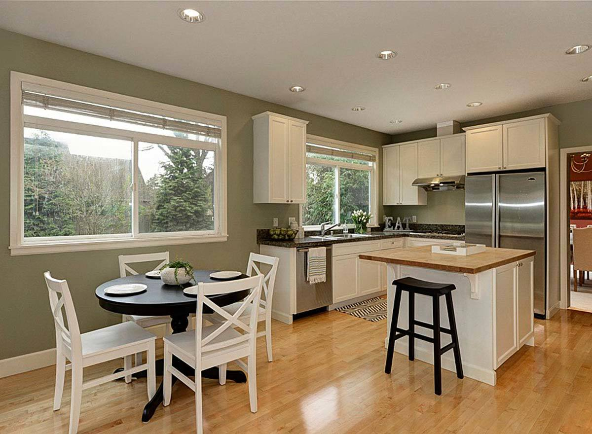 A farther view of the kitchen shows the breakfast nook with a round table and white chairs.