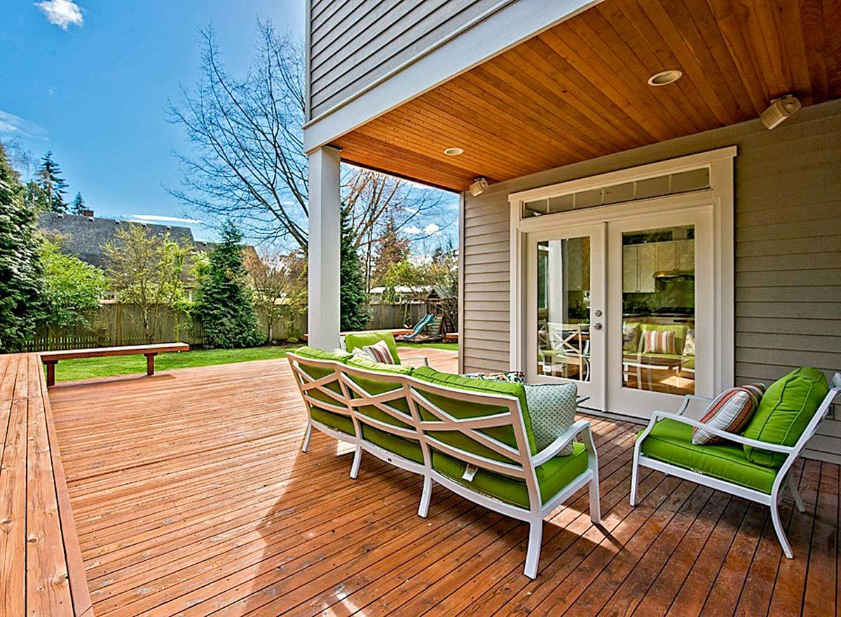 Covered patio with green cushioned seats and a wood-paneled ceiling matching with the wide plank floor.