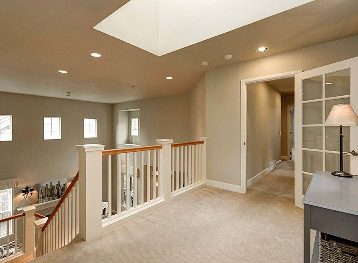 The second-floor loft has beige carpet flooring and a regular ceiling fitted with recessed lights and a skylight.