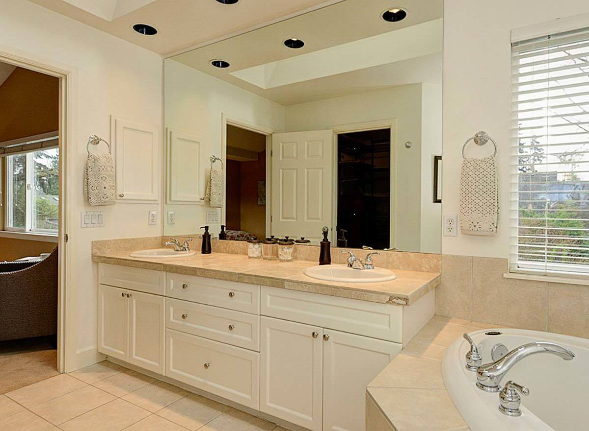The dual sink vanity has a beige marble countertop and a large frameless mirror.
